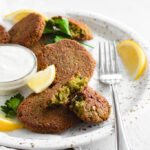 crispy baked falafel served in a plate with a dipping sauce