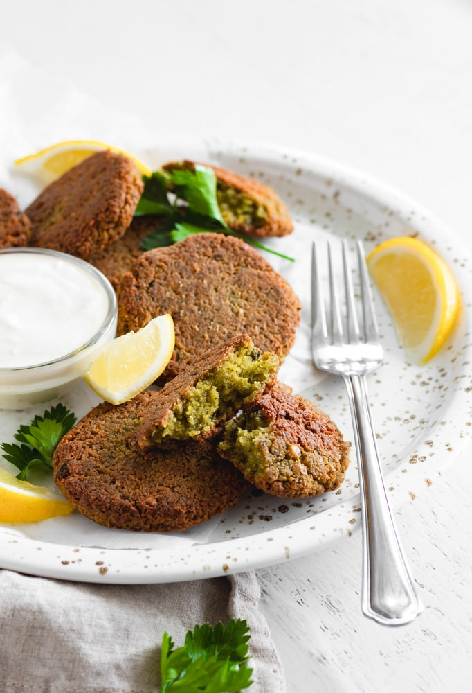 Crispy baked falafel patties on a plate, garnished with lemon slices and cilantro leaves.