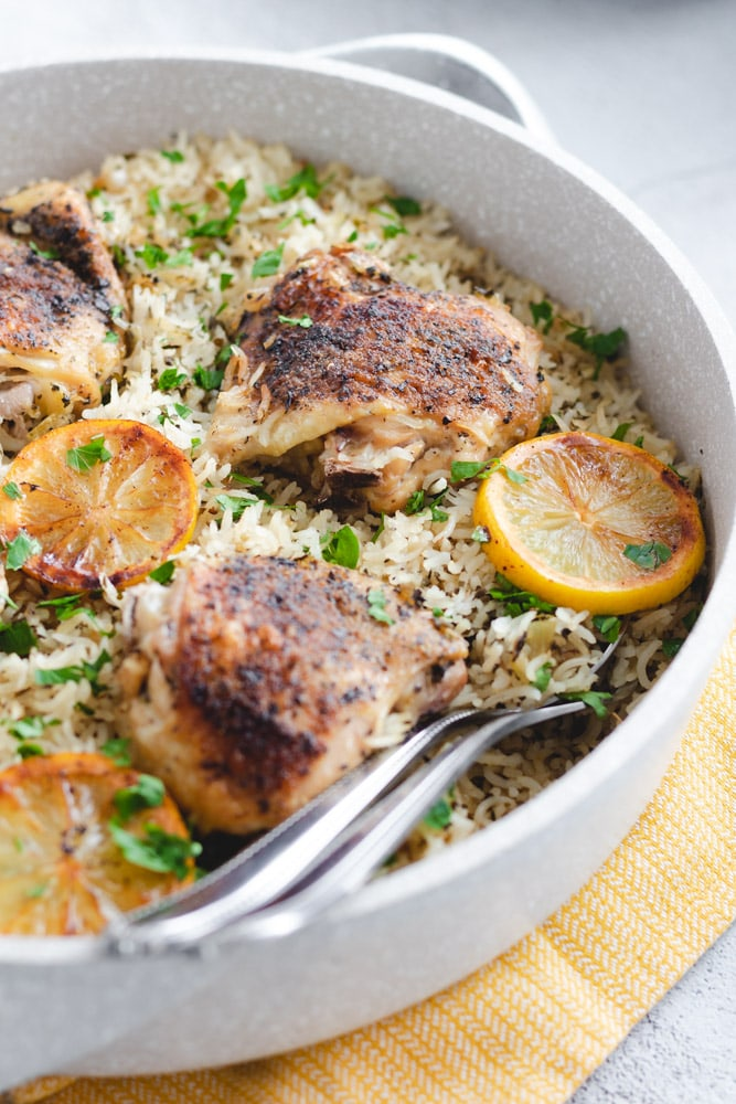 Chicken thighs served on a bed of fluffy rice, garnished with parsley and lemon slices.