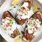 Stuffed eggplants placed on a plate drizzled with yogurt and garnished with nuts