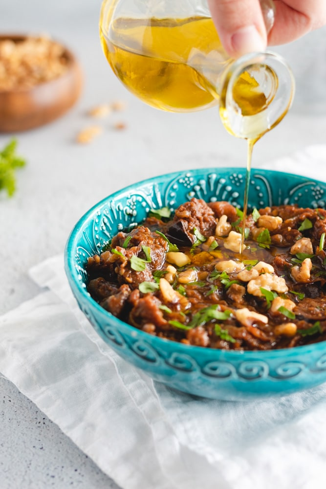 Eggplant dip served in a blue bowl, garnished with walnuts and parsley.