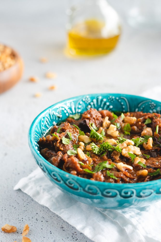 Eggplant dip served in a blue bowl, garnished with walnuts and parsley