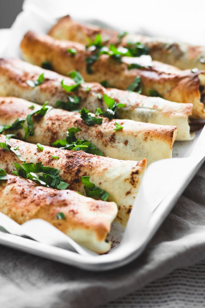 pita bread rolls served on an oven tray, garnished with parsley.
