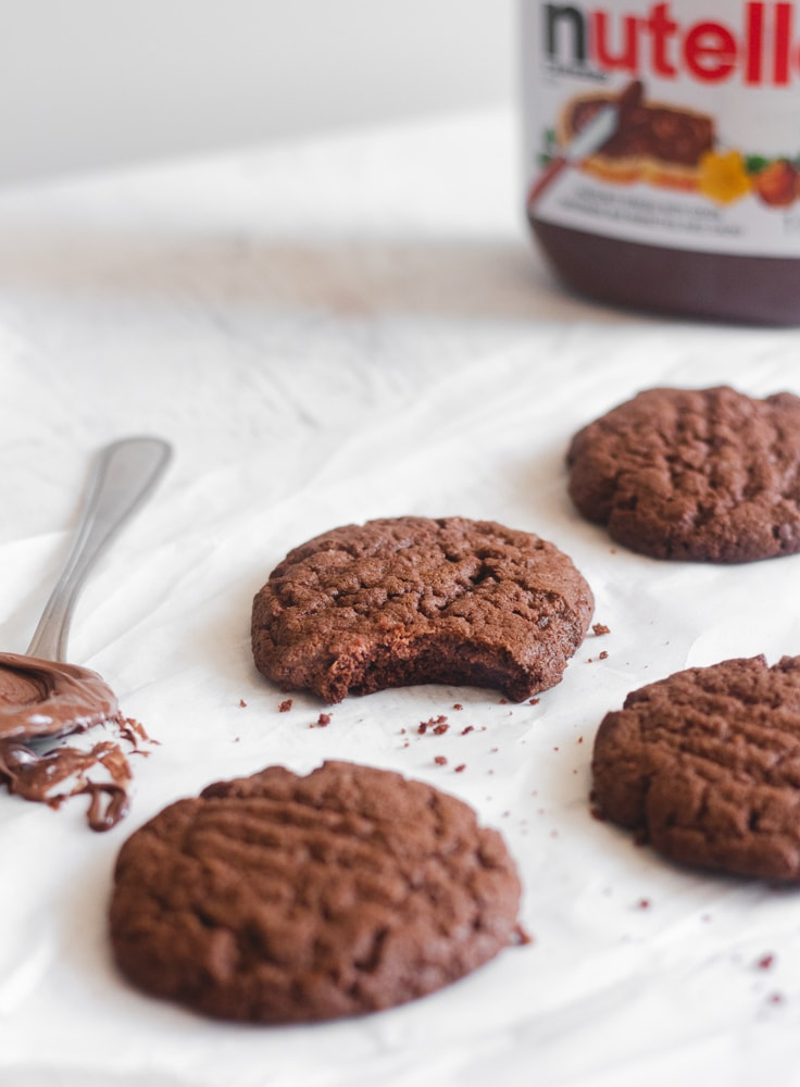 Nutella cookies on parchment paper with a spoonful of Nutella next to them and a jar of Nutella to the back