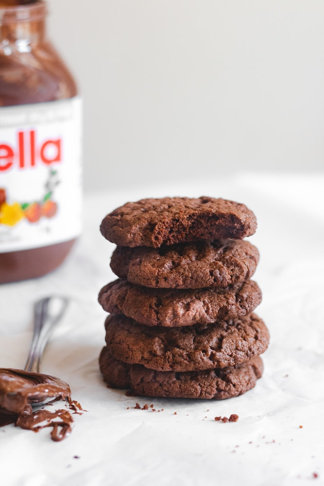 Nutella cookies stacked on top of each other with a spoonful of Nutella to the left and a jar of Nutella to the back