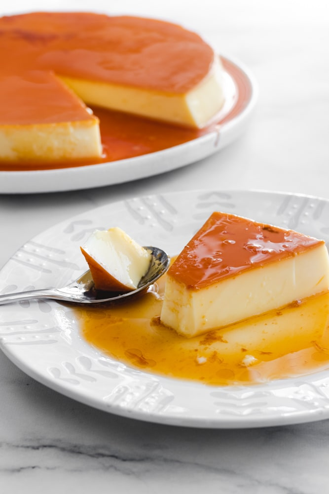 Creme caramel slice served on a white plate.