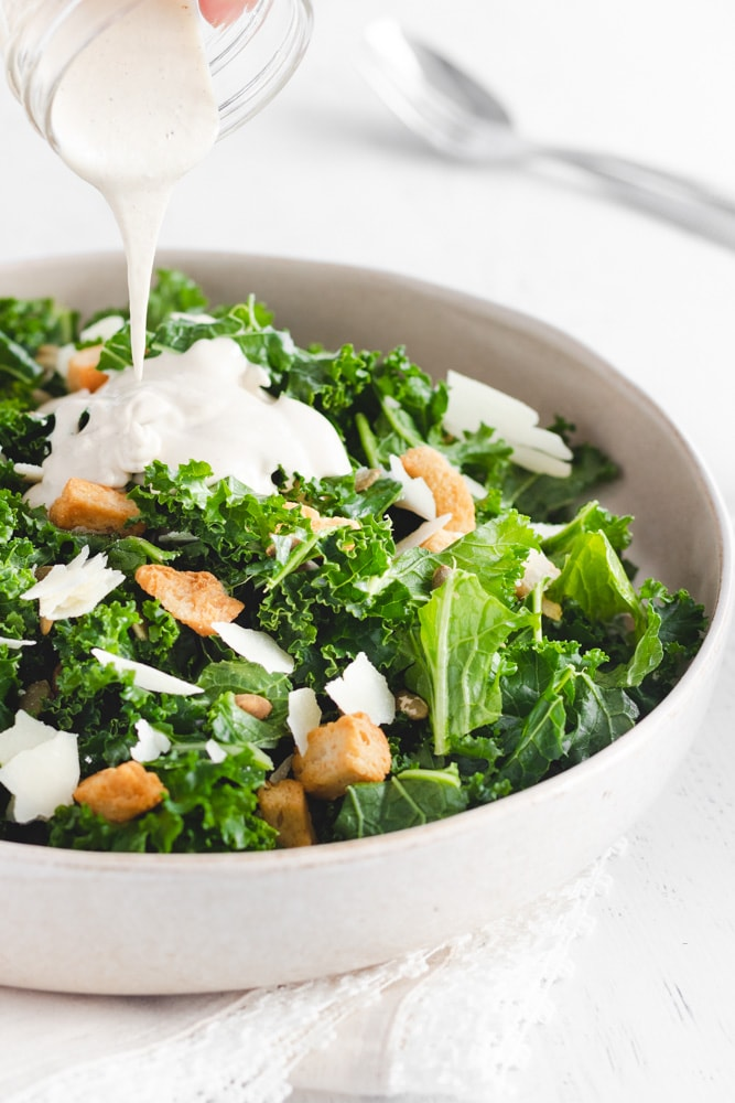 Kale Tahini Salad served in a large serving dish with Tahini Salad dressing being poured on top