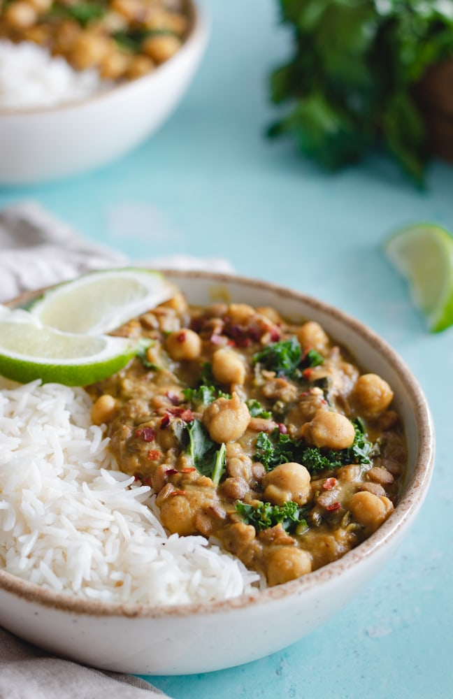 Chickpea Curry served on top of rice and garnished with lemon wedges