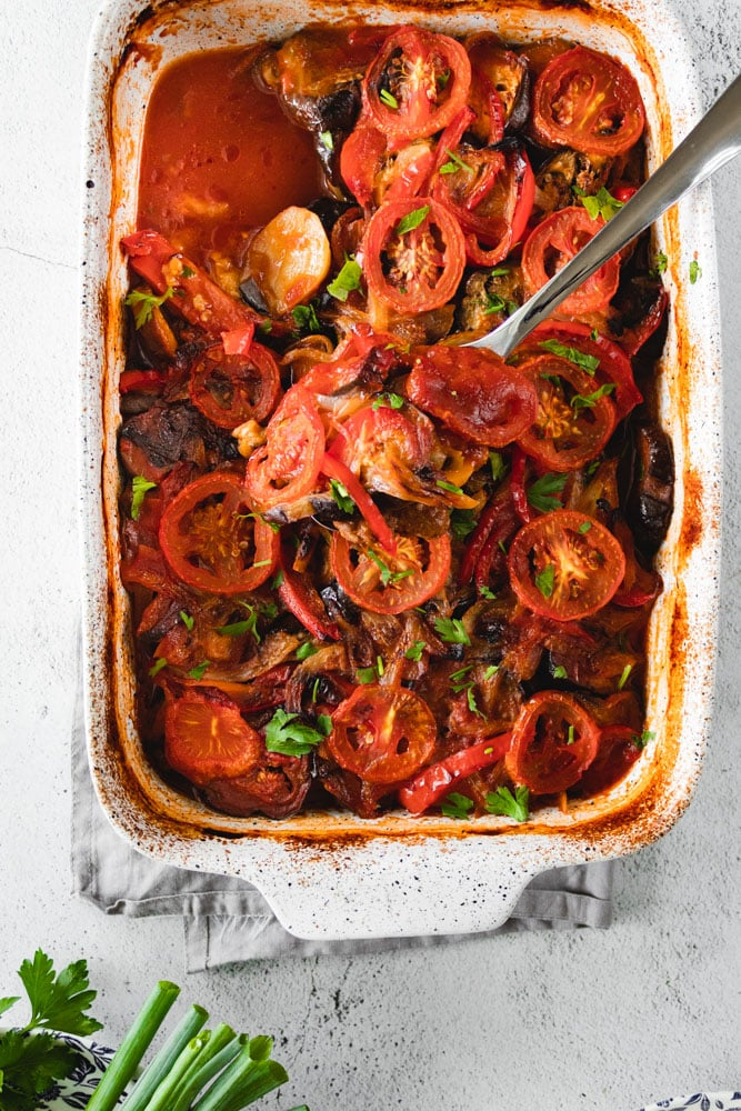 Mediterranean Eggplant Casserole in a baking dish with a serving spoon