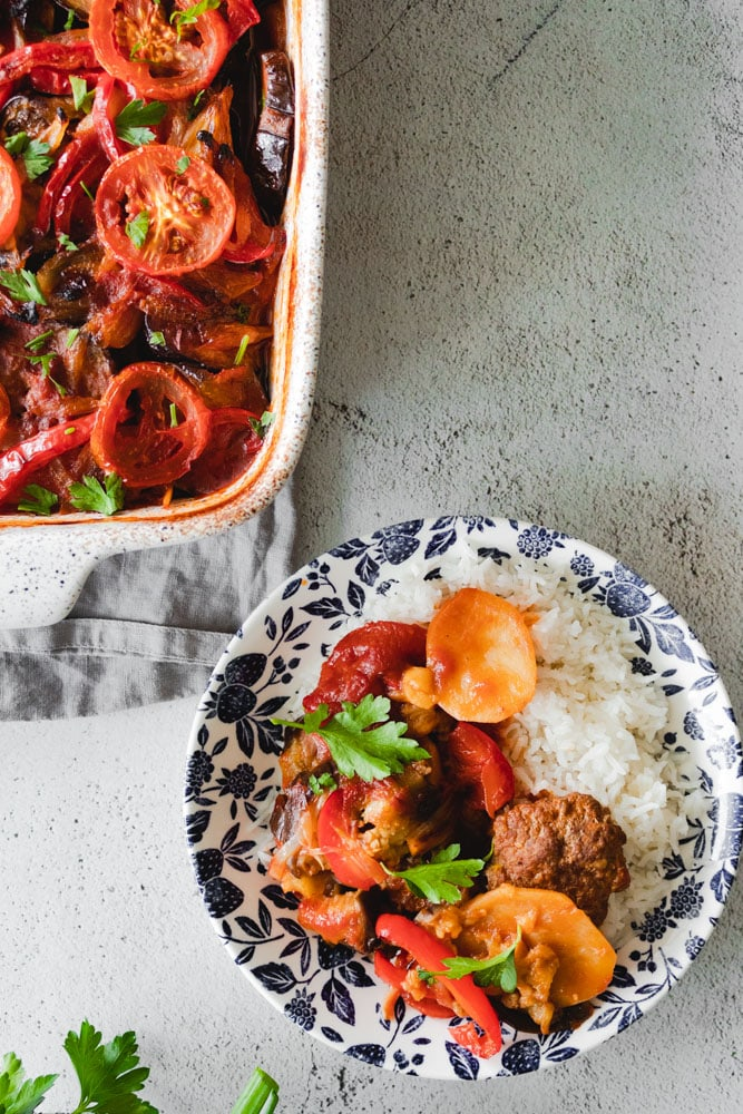 Mediterranean Eggplant Casserole in a baking dish as well as served in a small plate over rice