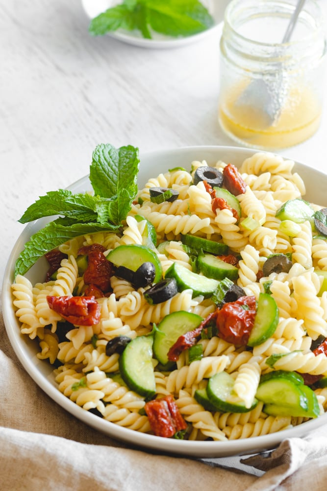 vegan Mediterranean pasta salad served in a bowl garnished with mint