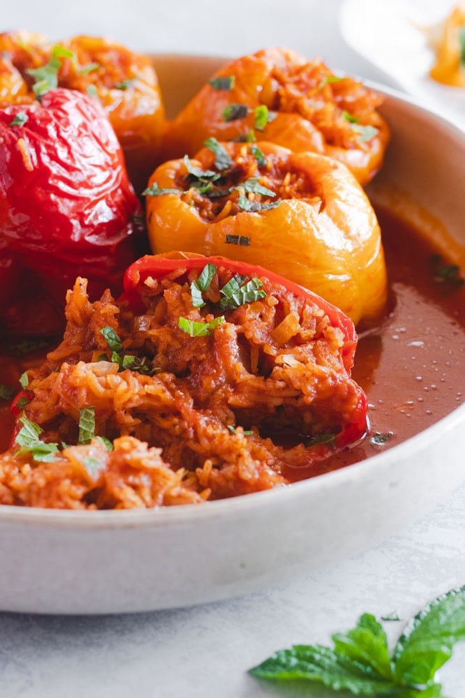 Mediterranean stuffed peppers in a serving dish garnished with chopped mint