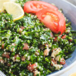 Tabouli Salad served in a bowl with lemon and tomato slices