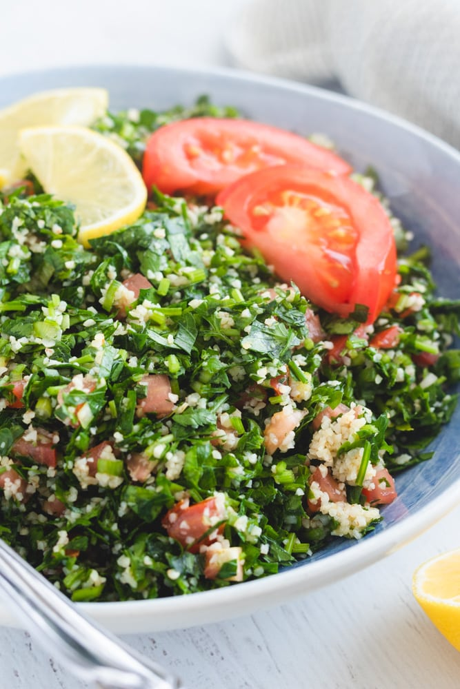 Tabouli salad served in a plate garnished with lemon and tomato slices