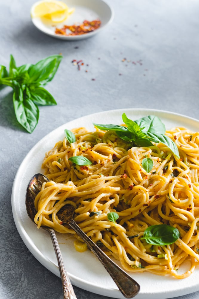 Tahini pasta served in a white plate garnished with basil leaves and chilli flakes