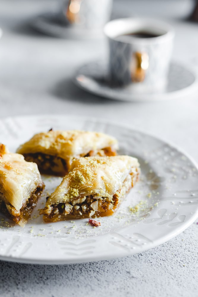 Three pieces of Baklawa or Baklava cut into diamond shapes and garnished with ground pistachio and dried rose petals
