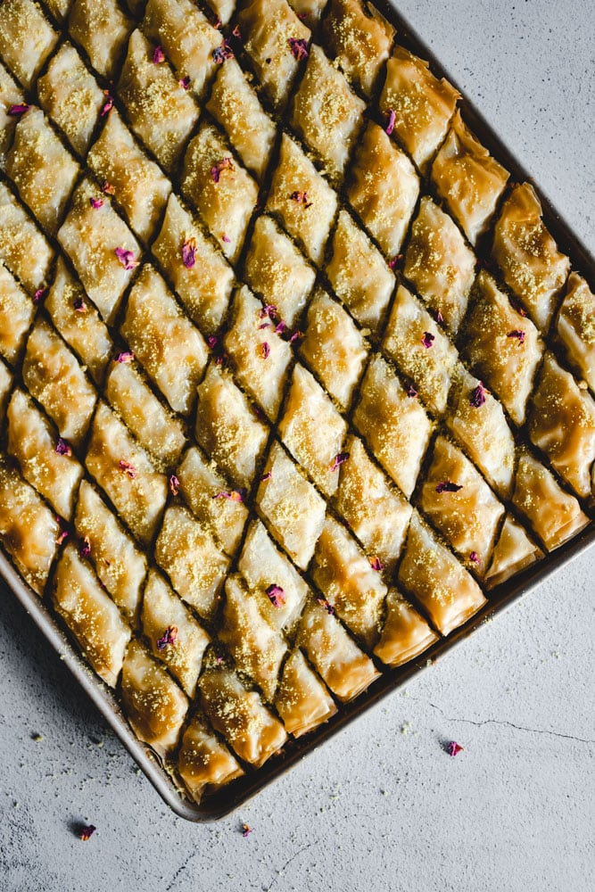 Tray of Baklawa or Baklava cut into diamond shapes and garnished with ground pistachio and dried rose petals