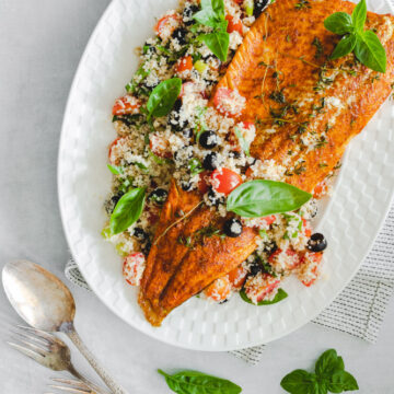 Rainbow trout fillet served over a bed of bulgur salad in a white plate, with a serving spoon and basil