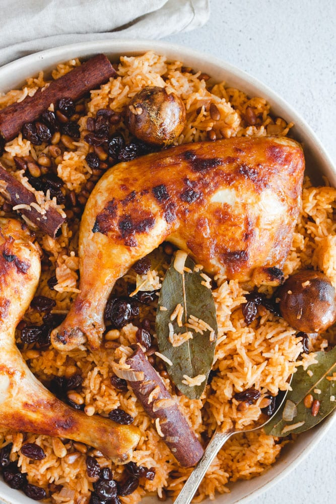 Chicken Machboos served in a dish topped with chicken legs, pine nuts, raisins and whole spices