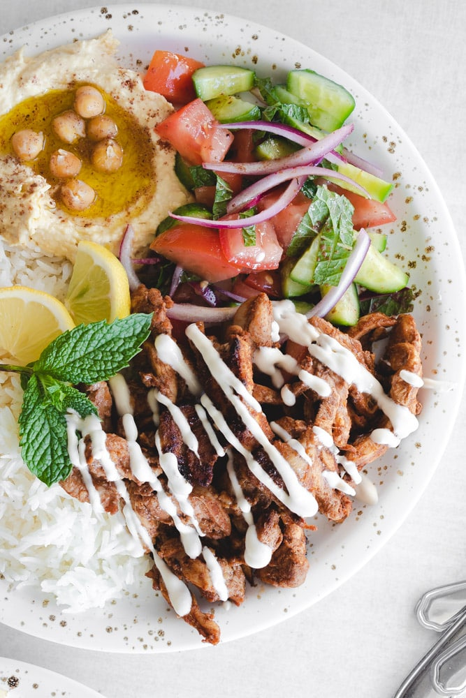 Chicken Shawarma plate with hummus, rice, chicken, and a salad