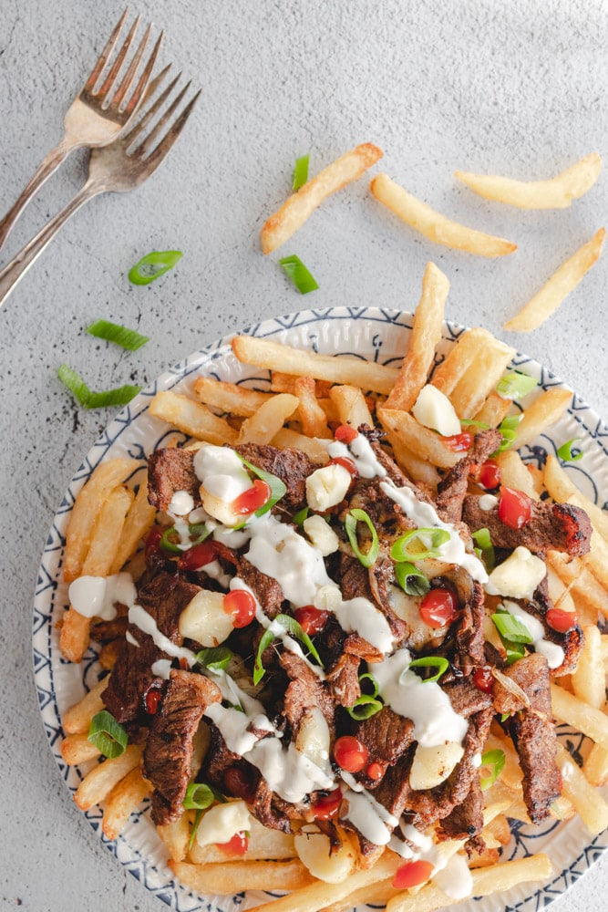 Beef shawarma poutine served in a plate with someone about to dig in using a fork