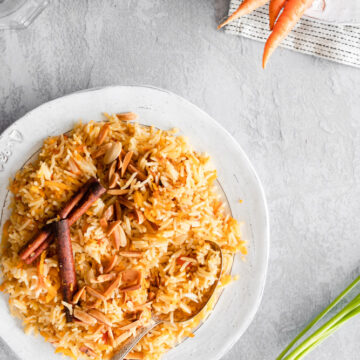 Carrot rice served in a white plate, garnished with almonds and cinnamon sticks