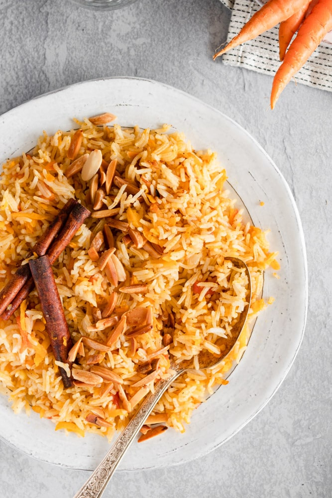 Carrot rice served in a white plate, garnished with friend almonds and cinnamon sticks on a grey background