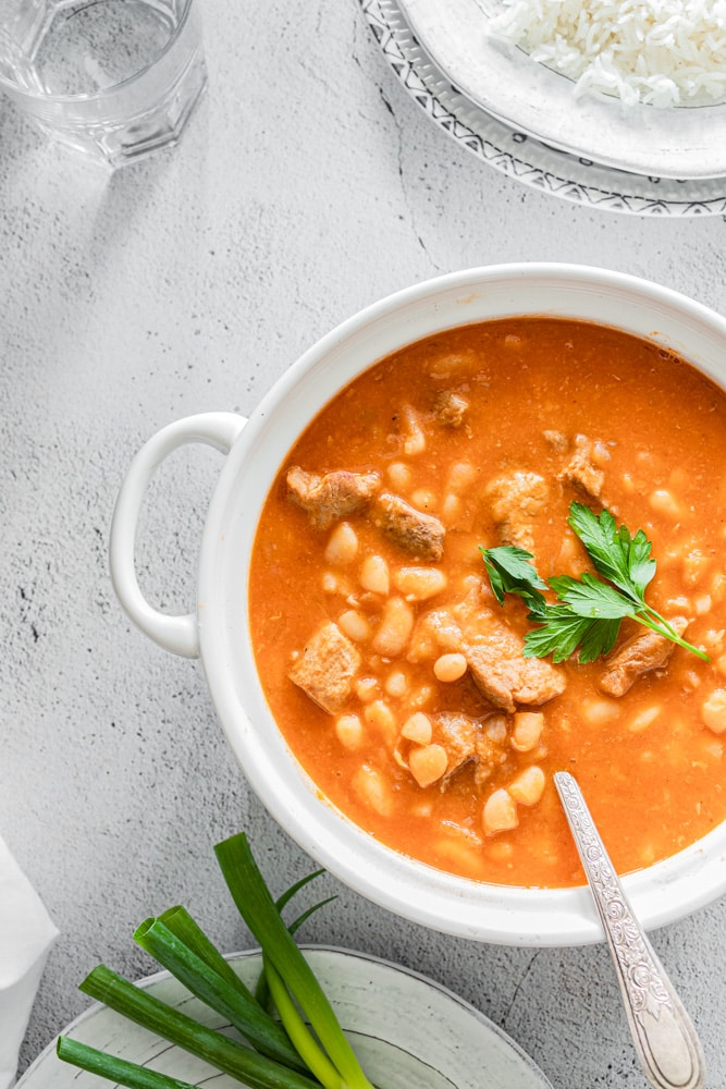 Fasolia white bean stew served in a white pot and garnished with parsely
