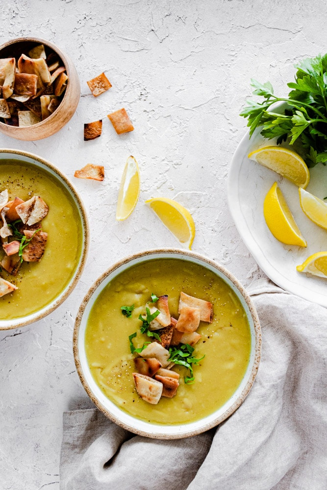 Arabic Lentil Soup served in bowls with crunchy pita and parsley on top