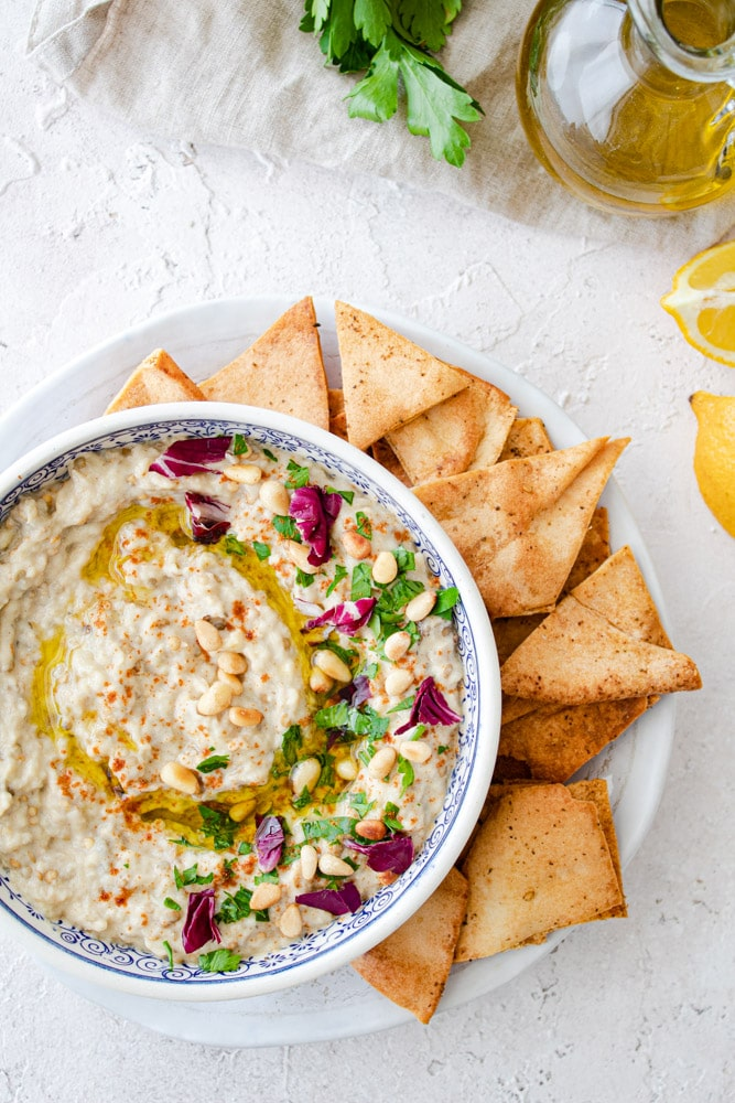 Baba ghanoush roasted eggplant dip served in a bowl with pita chips