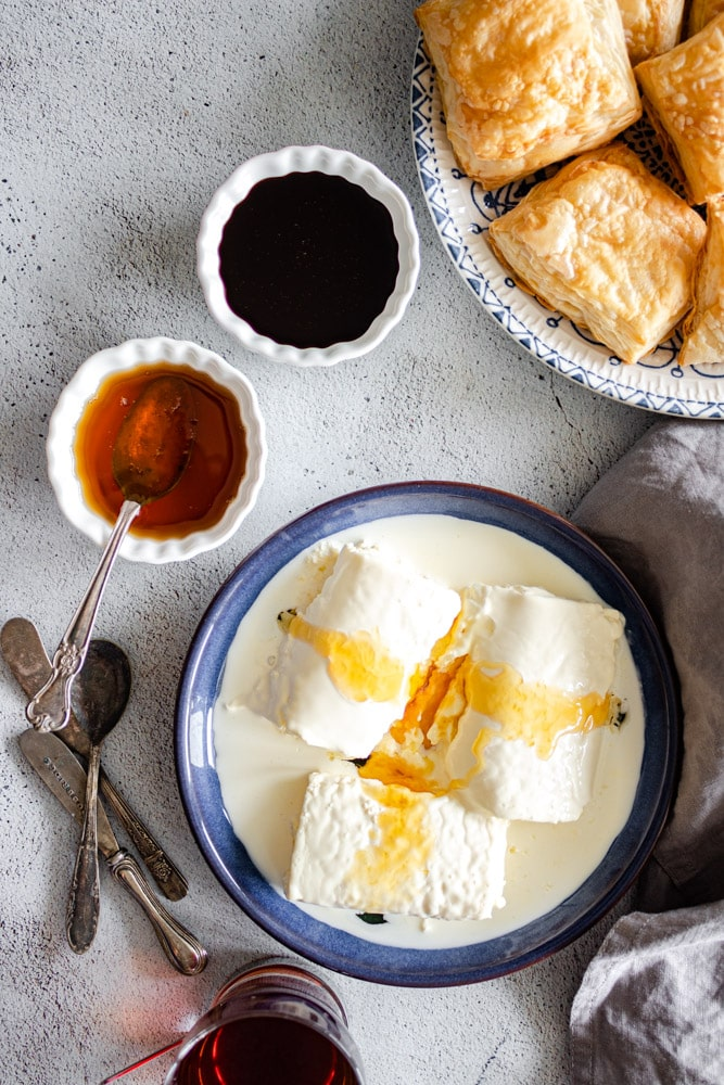 Geymar / Kaymak drizzled with honey, served with puff pastry kahi honey nad date molasses