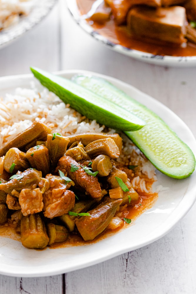 Okra stew served over rice with a side of cucumber