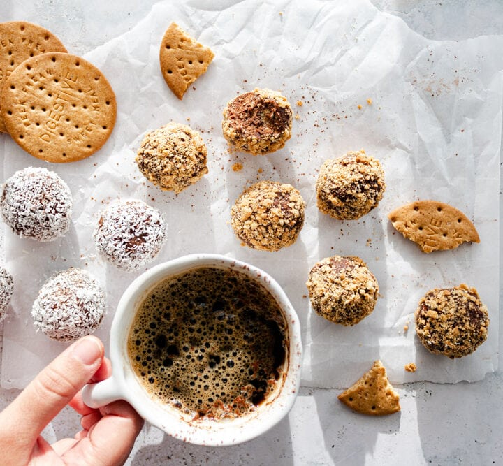 Chocolate biscuit balls on parchment paper with a coffee cup