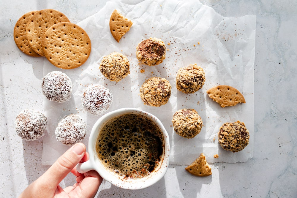 10 chocolate biscuit balls topped with crushed biscuits and shredded coconut placed on parchment paper around a cup of coffee. A hand holds the handle of the coffee. Three digestive biscuits are in the top left corner.