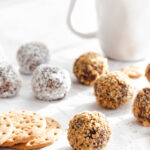 Biscuit balls on parchment paper with a white coffee mug in the back and digestive biscuits on the left side
