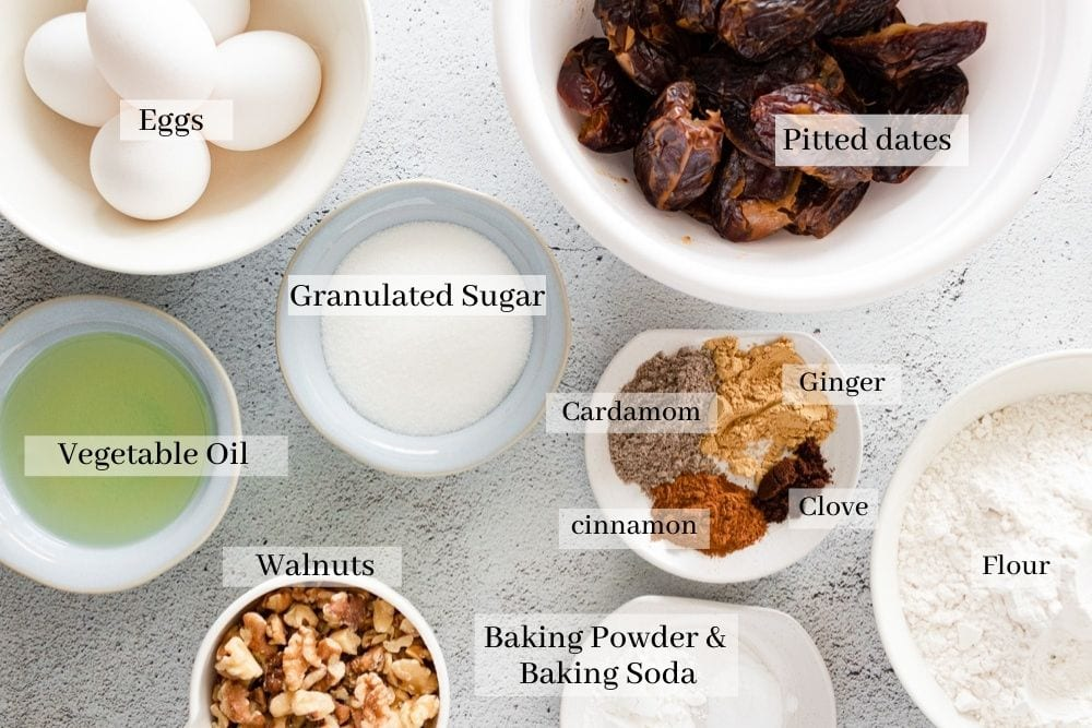 Ingredients for date cake which are pitted dates, eggs, granulated sugar, vegetable oil, flour, baking powder, baking soda, walnuts, cardamom, cinnamon, clove, and ginger