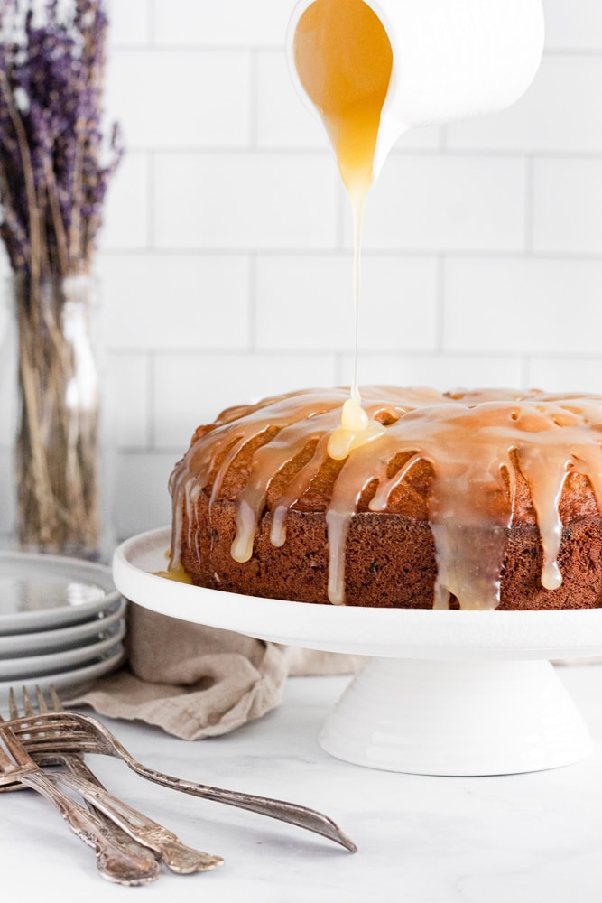Date and walnut cake with a butter glaze being poured on top, a stack of plates and forks in the corner