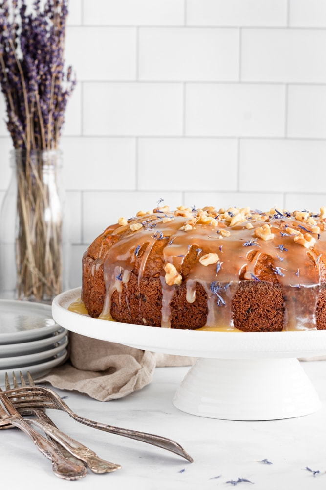 Date and walnut cake with a butter glaze served on a cake stand and decorated with walnuts and flower petals