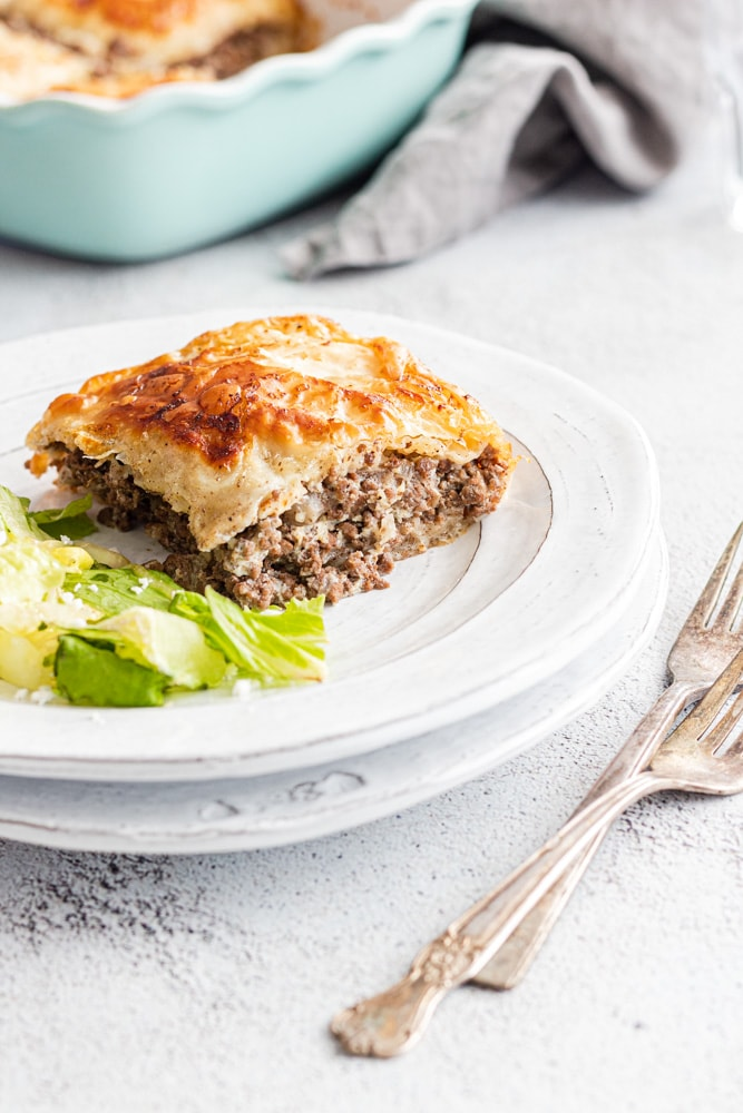 Egyptian goulash meat pie served on a white plate with a green side salad