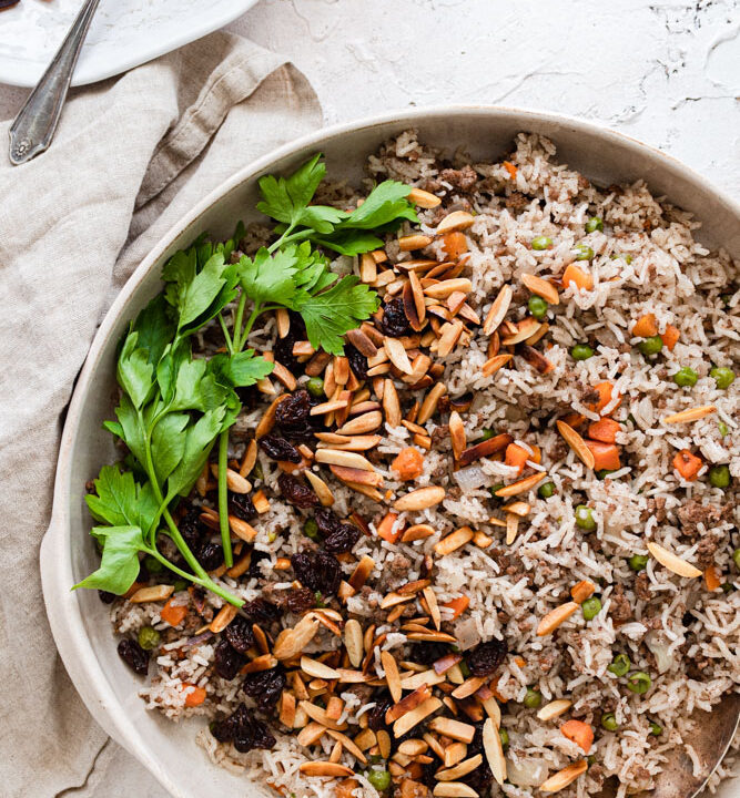Hashweh rice served in a platter garnished with almonds, raisins and parsley