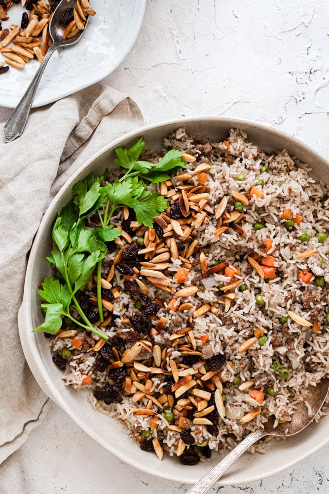 Hashweh rice served in a platter and garnished with toasted almonds, raisins and parsley. A plate of almonds and raisins with a spoon is in the top left corner.