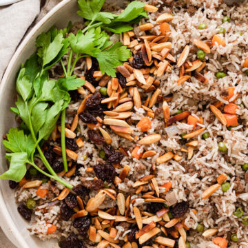 Hashweh rice served in a platter and garnished with almonds, raisins and parsley