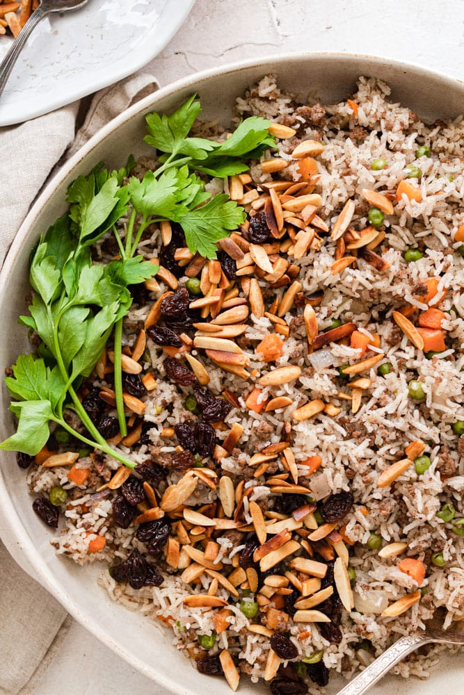 Hashweh rice served in a platter and garnished with toasted almonds, raisins and parsley