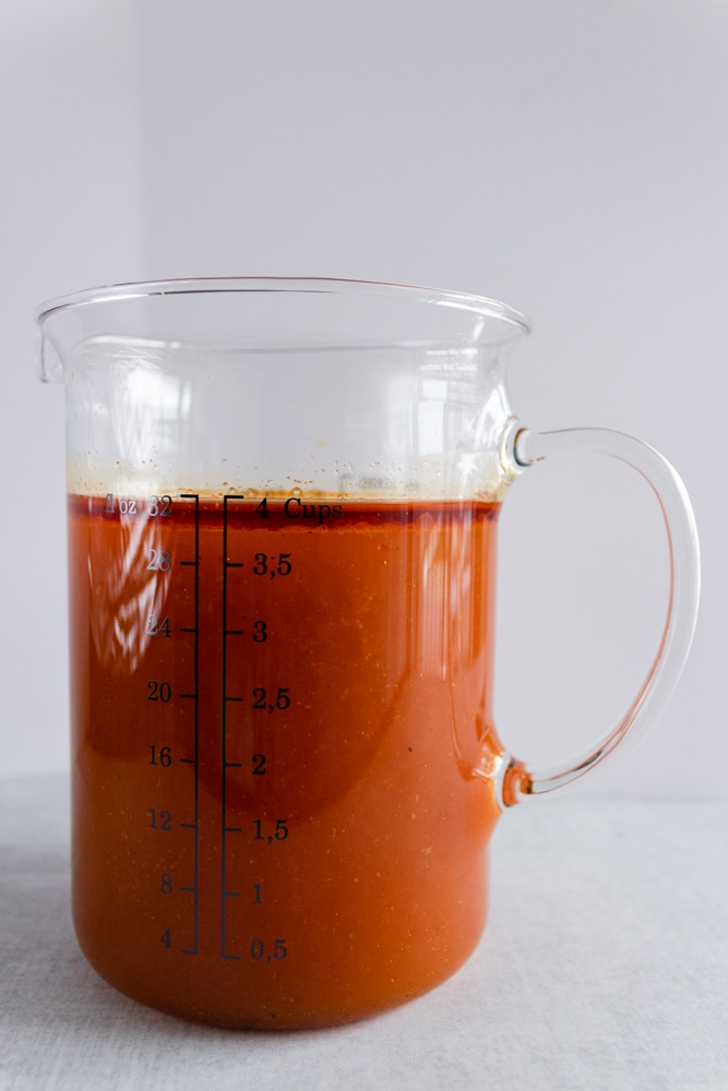 Red broth in a measuring cup