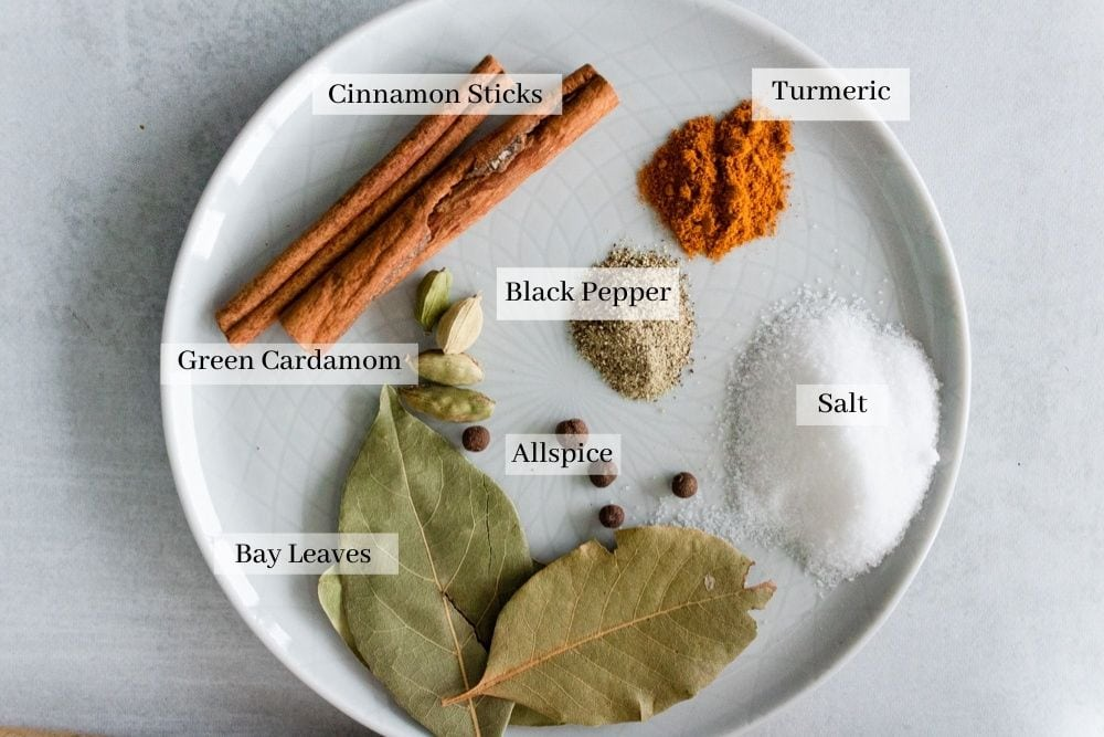 Spices used for maqluba which are cinnamon sticks, green cardamom, bay leaves, allspice, salt, black pepper, and turmeric