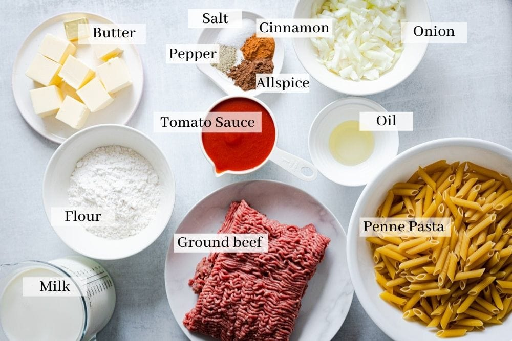 Ingredients needed for bechamel pasta bake: butter, flour, milk, tomato sauce, ground beef, penne pasta, oil, onion, cinnamon, allspice, pepper