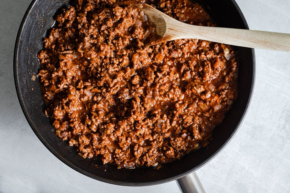 Meat sauce in a black pan with a wooden spoon