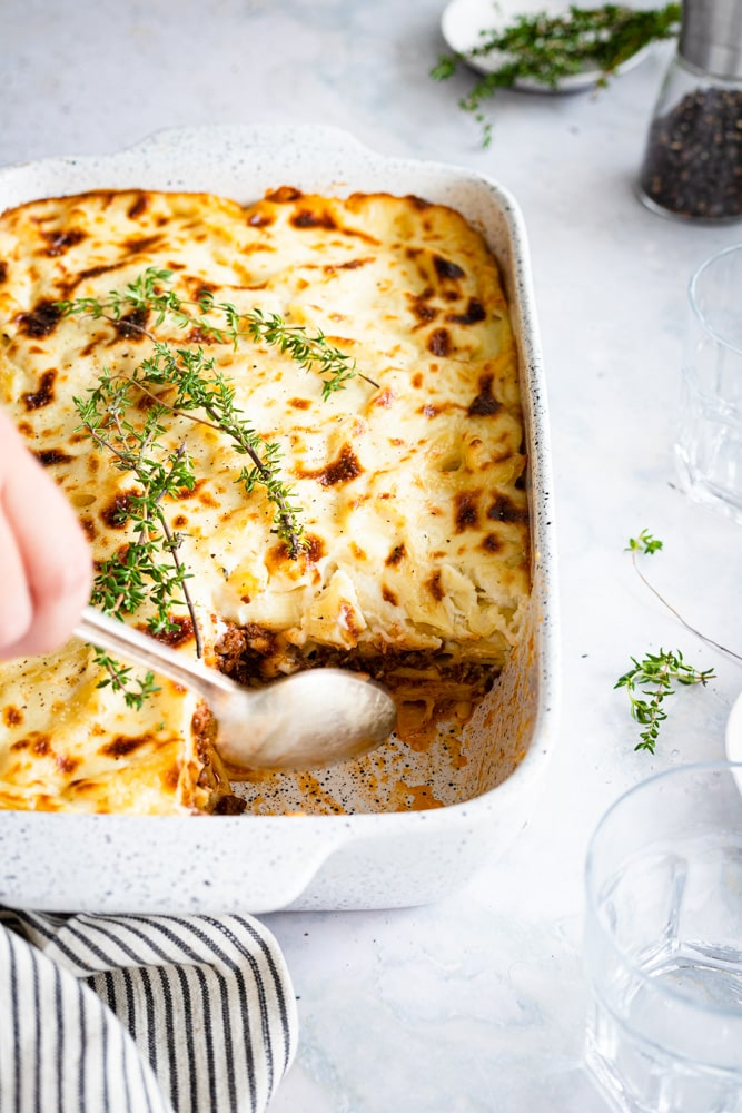 Bechamel Pasta bake served in a large casserole with one piece taken out using a spoon