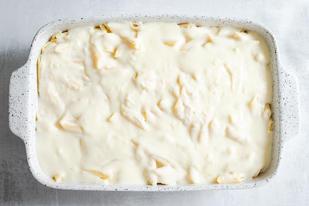 Pasta in a casserole covered in bechamel sauce, before baking