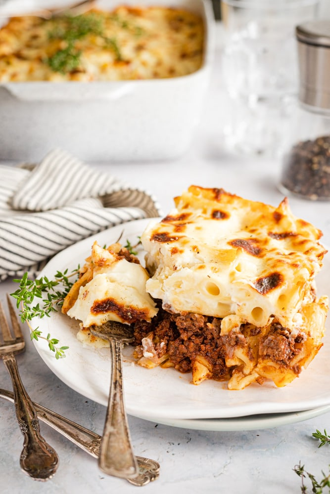 A slice of Bechamel Pasta bake on a plate with a piece cut out using a fork